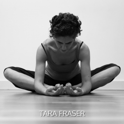 Tara Fraser, director of Yoga Junction in a seated position with her legs crossed and her hands on the floor with the palms facing upwards